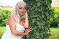 Ładna kobieta w biały smokingowy opierać przeciw drzewu Fotografia Stock
