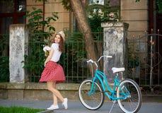 Ładna kobieta w czerwieni sukni chwytów kwiatach z błękitnym rocznika rowerem blisko jej pozyci przed pięknym starym domem obrazy royalty free