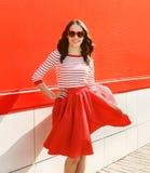 Ładna kobieta w czerwonych okularach przeciwsłonecznych i sukni przeciw kolorowemu zdjęcia stock
