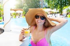 Ładna kobieta w kapeluszowym cieszy się koktajlu w pływackim basenie Fotografia Royalty Free