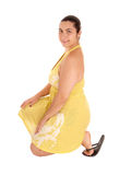 Ładna kobieta w kolor żółty sukni klęczeniu Obrazy Stock