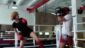 Ładna kobieta w sportswear pracie przy cios techniką z trenerem przy bokserskim pierścionkiem zbiory wideo