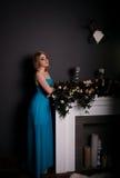 Ładna kobieta w wieczór sukni pozuje nad ciemnym tłem Obrazy Royalty Free