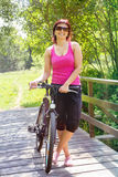 Ładna kobieta z bicyklem na małym drewnianym moscie Zdjęcia Royalty Free