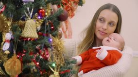 Ładna kobieta z dwumiesięczną córką dekoruje choinki zbiory wideo