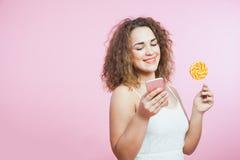 Ładna kobieta z kędzierzawego włosy smartphone i lizakiem obrazy royalty free
