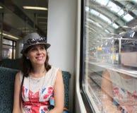 Ładna kobieta z kapeluszowym obsiadaniem w pociągu w staci zdjęcia royalty free