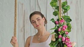 Ładna kobieta z makijażem i fryzura na huśtawce dekorowaliśmy z kwiatami zdjęcie wideo
