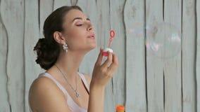 Ładna kobieta z pięknym makijażem i eleganckim fryzury dmuchaniem gulgocze zbiory wideo