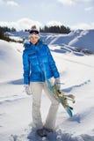 Ładna kobiety pozycja z snowboard w jej ono uśmiecha się i nand zdjęcia stock