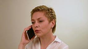 Ładna krótkiego włosy dziewczyna opowiada telefonem komórkowym zdjęcie wideo