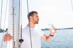 Ładna mężczyzna woda pitna na jachcie Fotografia Stock