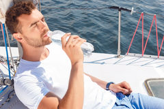 Ładna mężczyzna woda pitna na jachcie Obrazy Royalty Free