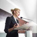 Ładna, młoda biznesowa kobieta daje prezentaci, obrazy stock
