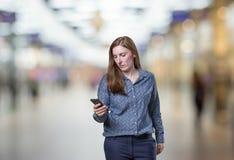 Ładna młoda biznesowa kobieta opowiada Mobil telefon nad plamy bac Zdjęcia Stock