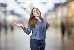 Ładna młoda biznesowa kobieta wątpliwość nad plamy tłem Fotografia Royalty Free