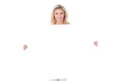 Ładna młoda blondynka pokazuje plakat Obraz Stock