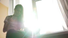 Ładna młoda blondynki dziewczyna je tort i podrzucać przez książkowego obsiadania na windowsill zdjęcie wideo