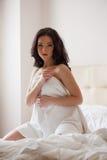 Ładna młoda brunetka odpoczywa w hotelowej sypialni Zdjęcia Stock