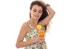 Ładna młoda brunetka w sarafant z kwiecistych wzorów napojów świeżym pomarańczowym koktajlem z zamkniętymi oczami odizolowywający Obrazy Royalty Free