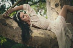 Ładna młoda ciemnego włosy kobieta w romantycznym smokingowym kłamstwie na drzewie wewnątrz Fotografia Stock