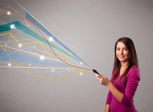 Ładna młoda dama trzyma telefon z kolorowym abstraktem wykłada a Fotografia Stock