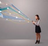 Ładna młoda dama trzyma telefon z kolorowym abstraktem wykłada a Obrazy Royalty Free