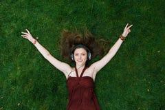 Ładna młoda dziewczyna kłama na trawie słucha muzykę w hełmofonach Fotografia Stock