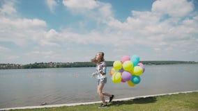 Ładna młoda dziewczyna pokazuje szczęśliwe emocje z balonami w ręce przy coustline zbiory wideo