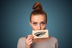 Ładna młoda dziewczyna trzyma biel kartę z uśmiechu rysunkiem zdjęcia stock