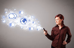 Ładna młoda dziewczyna trzyma telefon z ogólnospołecznymi medialnymi ikonami Obrazy Royalty Free