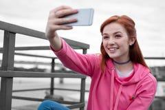 Ładna młoda dziewczyna uśmiecha się selfies samotnie i bierze zdjęcia royalty free