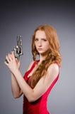 Ładna młoda dziewczyna w czerwieni sukni z pistoletem odizolowywającym Zdjęcia Royalty Free