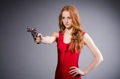Ładna młoda dziewczyna w czerwieni sukni z pistoletem odizolowywającym Obraz Stock