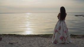 Ładna młoda dziewczyna w długiej pięknej sukni chodzi rzeką zbiory