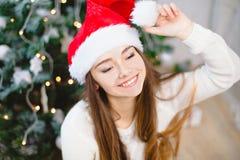 Ładna młoda dziewczyna w Santa Claus kapeluszu siedzi i ono uśmiecha się blisko choinki w czerwonych skarpetach, tła bokeh muzycz Zdjęcia Royalty Free