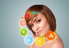 Ładna młoda dziewczyna z kolorowymi witamin ikonami, symbolami i zdjęcia royalty free