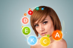 Ładna młoda dziewczyna z kolorowymi witamin ikonami, symbolami i obraz stock