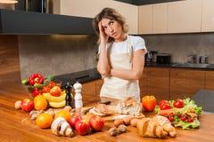 Ładna młoda gospodyni domowa męcząca i smutna w kuchni Fotografia Royalty Free