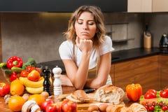 Ładna młoda gospodyni domowa męcząca i smutna w kuchni Obrazy Stock