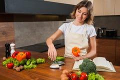 Ładna młoda gospodyni domowa waży ogórek na kuchennych ciężarach Obrazy Royalty Free
