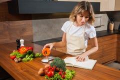 Ładna młoda gospodyni domowa waży paprica na kuchennych ciężarach Obrazy Stock