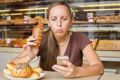 Ładna młoda kobieta czyta wiadomość na łasowanie chlebie i telefonie Fotografia Stock