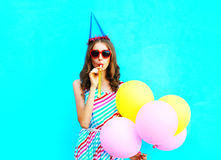 Ładna młoda kobieta dmucha gwizd w urodzinowej nakrętce trzyma lotniczych kolorowych balony zdjęcie stock