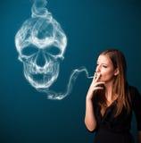 Młoda kobieta dymi niebezpiecznego papieros z toksycznym czaszka dymem Obraz Royalty Free