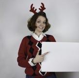 Ładna młoda kobieta jest ubranym poroże i trzyma znaka Zdjęcie Stock