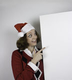 Ładna młoda kobieta jest ubranym Santa kapelusz i trzyma puste miejsce znaka Obrazy Stock