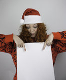 Ładna młoda kobieta jest ubranym Santa kapelusz i trzyma puste miejsce znaka Obrazy Royalty Free