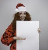 Ładna młoda kobieta jest ubranym Santa kapelusz i trzyma puste miejsce znaka Zdjęcia Royalty Free