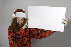 Ładna młoda kobieta jest ubranym Santa kapelusz i trzyma puste miejsce znaka Fotografia Royalty Free